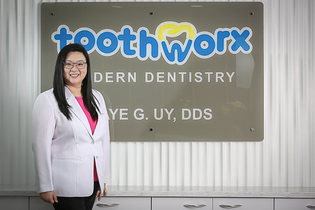 Picture of Dr. Faye Uy besides Toothworx Signage